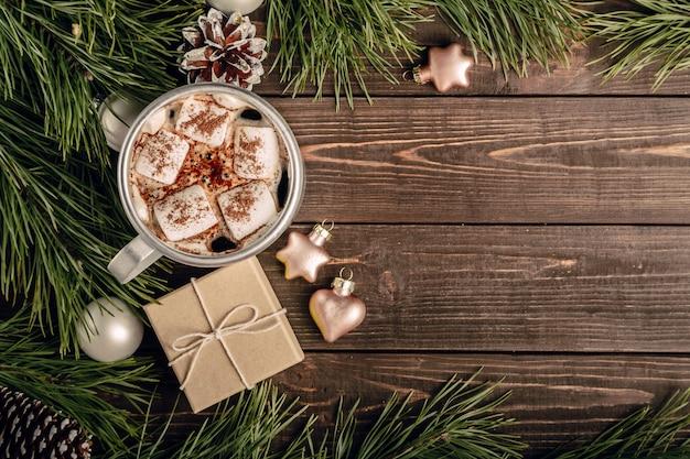 Café de malvavisco y regalo en la mesa de madera