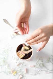 Café con malvaviscos y manos de mujer la vista desde arriba