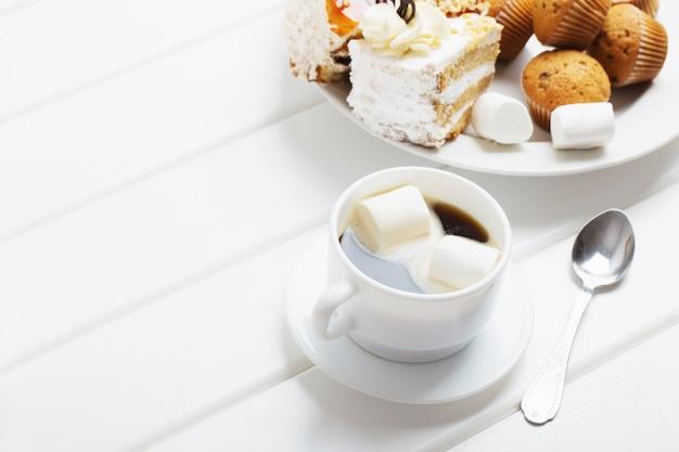 Café con malvaviscos y pastel sobre fondo blanco de madera