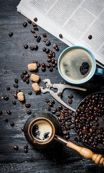 Café por la mañana. cafetera y un periódico con granos de café tostados alrededor de la mesa de madera.