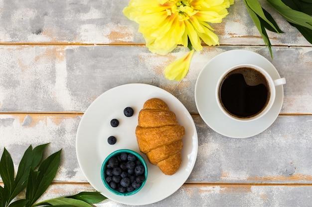 Café de la mañana, croissant, arándanos y hermosas flores de peonía amarilla en la mesa de luz