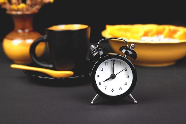 Café de la mañana, desayuno de granola con fruta cerca de despertador, flor de florero amarillo sobre fondo negro.