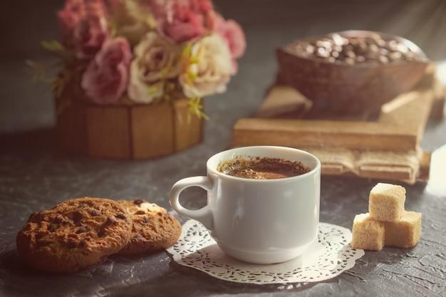 Café de la mañana con galletas y trozos de caña de azúcar en rayo de sol.