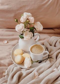 Café de la mañana con macarons y flores.