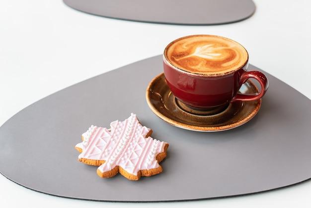 Café de la mañana en una taza de cerámica con espuma. pan de jengibre en forma de hoja de otoño.