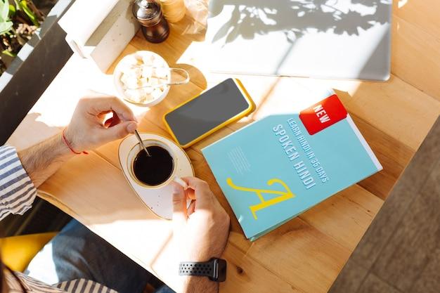 Café por la mañana. vista superior de un hombre revolviendo el azúcar en el café mientras está listo para comenzar su lección