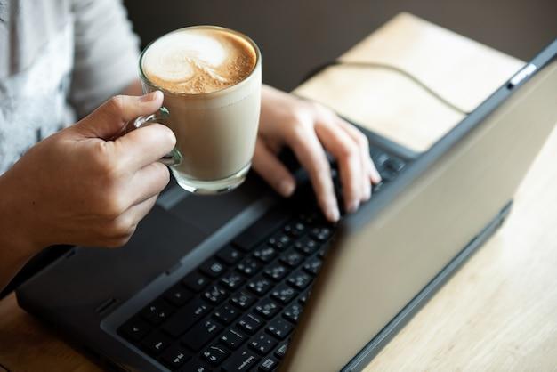Café en la mano oficina niña. ella está usando la computadora portátil.