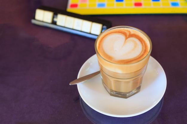Café marrón con café con leche, decorado con espuma de corazón.