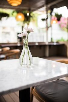 Café con mesas bajas y cojines verdes con orquídeas en las mesas.
