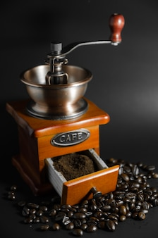 Café molido en molinillo de café con granos de café en vista vertical
