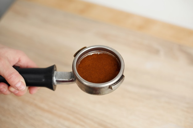 Café molido en primer plano apretado firmemente en el soporte para la máquina de café