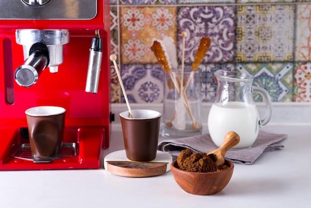Café molido en un tazón de madera, cafetera en la encimera
