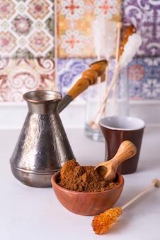 Café molido en un tazón de madera con palo de azúcar moreno
