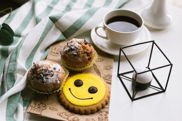 Café y muffin en superficie blanca