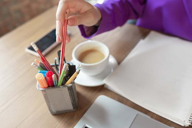 Café. mujer de negocios caucásica joven que trabaja en la oficina, parece elegante. papeleo, analizando, buscando desicion. concepto de finanzas, negocios, poder femenino, inclusión, diversidad, feminismo cerrar