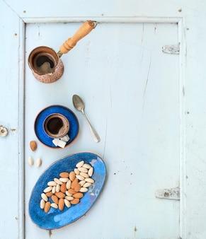 Café negro con almendras y pistachos sobre fondo azul claro. vista superior