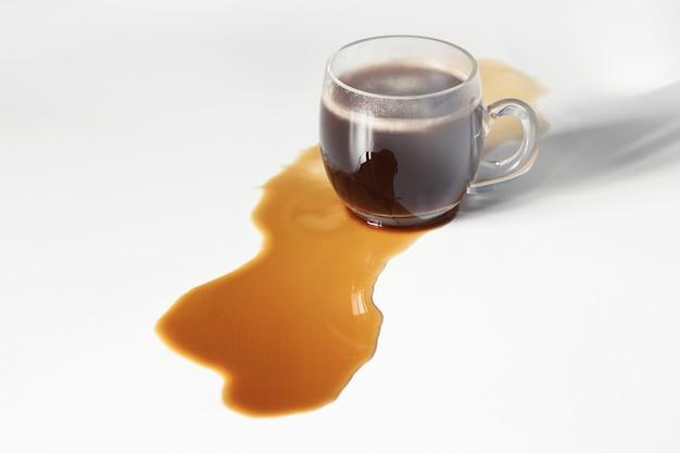 Café negro derramado sobre mesa blanca