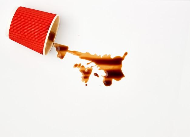 Café negro derramado de una taza de papel rojo