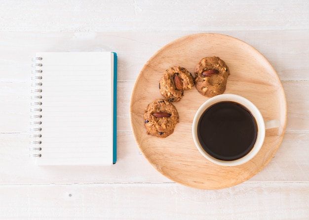 Café negro y galletas con portátil y cuaderno
