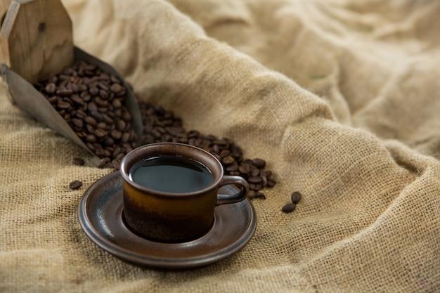 Café negro, granos tostados y boca en saco