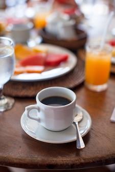 Café negro, jugo y frutas para el desayuno en una cafetería en el exótico resort