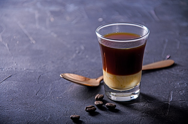 Café negro sobre superficie oscura con granos de café y cucharadita.