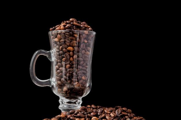 Café negro en la taza blanca y granos de café en fondo negro.