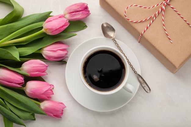 Café negro en taza blanca y tulipanes.