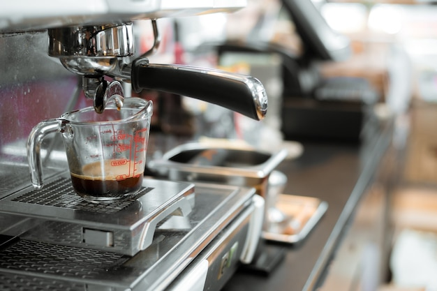Café negro en taza medidora poner cafetera