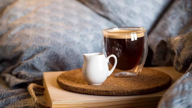 Café negro en una taza transparente en la cama en la mañana de otoño