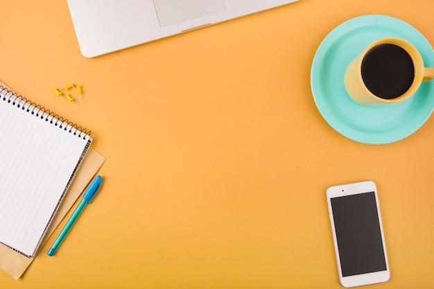 Café negro; teléfono inteligente; bolígrafo; chinchetas; portátil y bloc de notas en superficie naranja
