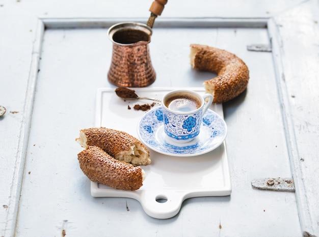 Café negro turco servido en una tradicional taza de cerámica con patrón, bagel de sésamo llamado simit en una tabla de servir blanca sobre una mesa de madera azul