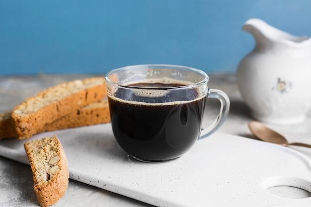 Café negro en vaso junto a rebanadas de pan con semillas