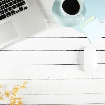 Café y notas adhesivas cerca de la computadora portátil y la ramita
