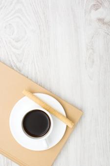 Café y oblea en libro y mesa de madera blanca