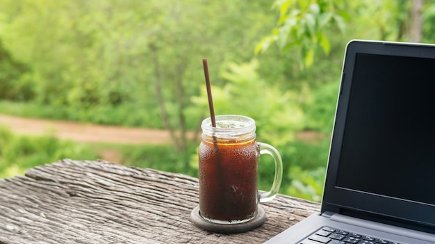 Café y ordenador portátil helados del americano en una tabla de madera.