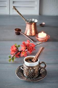Café oriental cocinado en una cafetera tradicional de cobre turco y servido en una taza a juego