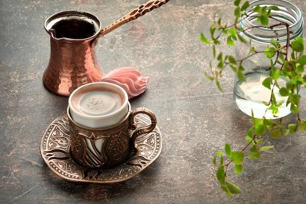 Café oriental cocinado en una olla tradicional de cobre turco vertido en una taza