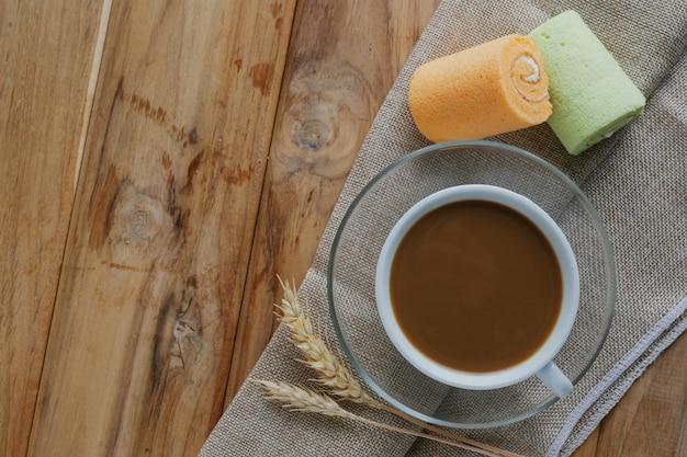 Café y pan colocados en suelos de madera marrón.