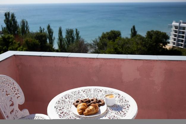 Café, pasteles y galletas en un plato en hermosa terraza con sillas y una mesa con una hermosa vista al mar