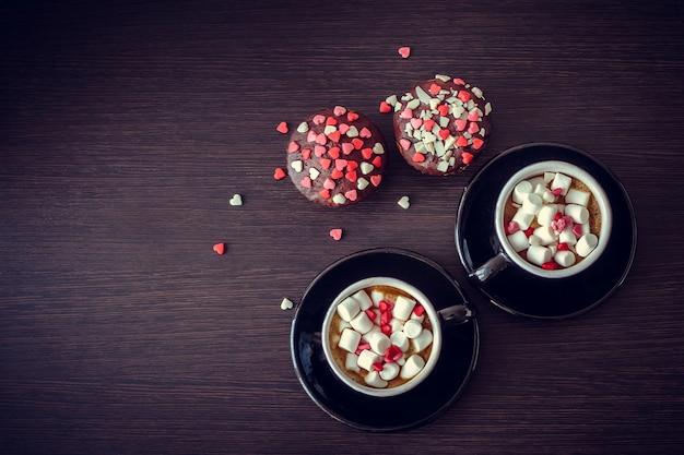 Café y pastelitos con corazones pequeños.