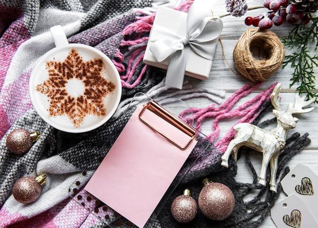 Café con patrón de copo de nieve sobre una cálida superficie de manta de lana, adornos navideños y un cuaderno para planes para el próximo año