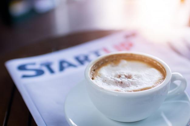 Café con periódico o revista en cafetería.