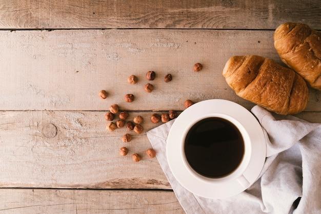 Café plano y croissant de desayuno con espacio de copia.