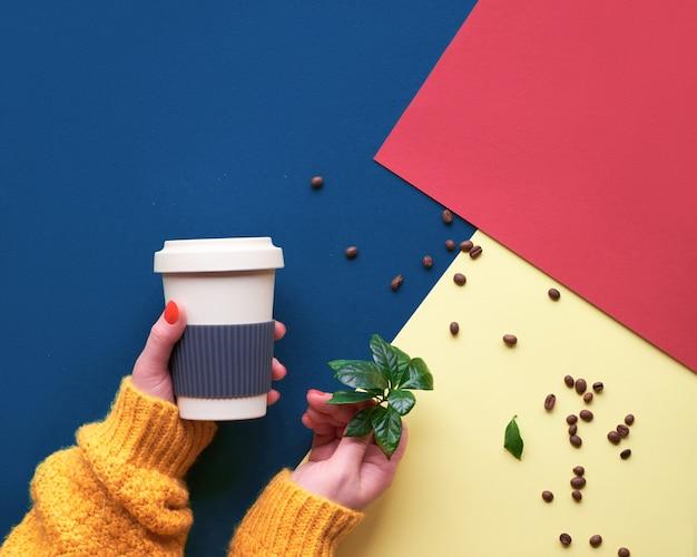 El café plano sin desperdicio yacía en papel dividido en tres tonos, rojo, azul y amarillo. eco amigable tazas de café reutilizables, manos en suéter naranja sosteniendo la taza y la planta de café.