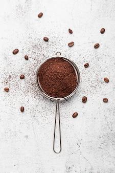 Café en polvo plano en un colador con granos