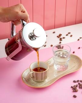 Café en prensa francesa con vaso de agua y granos de café en la mesa