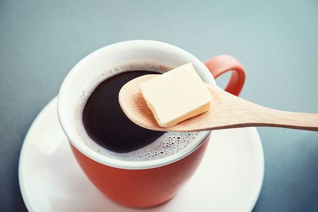 Café a prueba de balas, taza y mantequilla en una cuchara