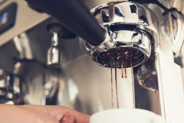Café que se elabora con la máquina que fluye hacia la taza.