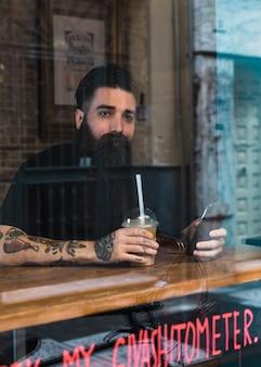 Café que se sienta empanado del hombre con el teléfono móvil y café a disposición